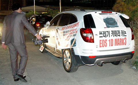 "A car belonging to a frustrated Korean photographer. The text on those banners translates to: ""Camera that is a piece of trash – Canon EOS 1D Mark 3"""