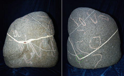A stone artifact with a drawing of a world map with an inlay of the All Seeing Eye. The location where this artifact was found is also marked on the map with an inlay (circled with green)